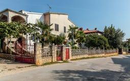 Opinión sobre casa de dos pisos del país con las puertas de la piedra gruesa y Foto de archivo libre de regalías
