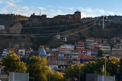 Opinión sobre el cablecarril debajo de los tejados de la ciudad vieja en la puesta del sol Tbilisi, Georgia Imágenes de archivo libres de regalías