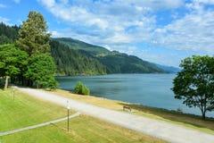 Opinión sobre el lago y las montañas Harrison con manera del paseo a lo largo de la orilla en frente fotografía de archivo
