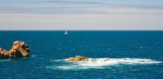 Opinión sobre el mar con las rocas y el yate rosados Imagenes de archivo