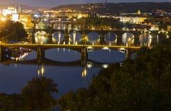 Opinión sobre el paisaje urbano de Praga así como los puentes que cruzan el río de Moldava que pasa a través del corazón de la ci Imagen de archivo libre de regalías