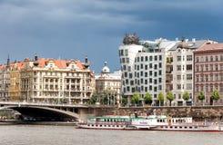Opinión sobre el río de Moldava, el puente y la construcción de viviendas famosa del baile en Praga Imagenes de archivo