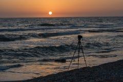 Opinión sobre el trípode y la playa tropical en puesta del sol Fotos de archivo