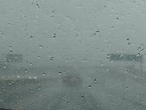 Opinión sobre la carretera a través de la ventana mojada Fotos de archivo