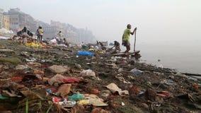 Opinión sobre la gente que pasa a través de basura en la orilla sucia del río el Ganges almacen de metraje de vídeo