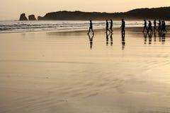 Opinión sobre la silueta de las personas que practica surf del grupo de personas que calientan la subida al océano en salida del  Imágenes de archivo libres de regalías