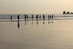 Opinión sobre la silueta de las personas que practica surf del grupo de personas que calientan la subida al océano en salida del  Foto de archivo
