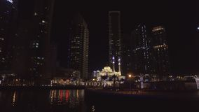 Opinión sobre pequeña mezquita magnífica en el puerto deportivo de Dubai, visión de la noche desde el barco de placer flotante almacen de video