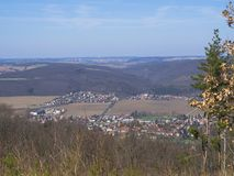 Opinión sobre pueblo en brdy en República Checa con los árboles, los edificios y las colinas, primavera temprana, SK azul Fotos de archivo libres de regalías