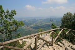 Opinión sobre San Marino a través de árboles de una colina imagenes de archivo