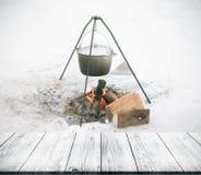 Opinión sobre un fuego en la nieve de la pasarela, de la tabla o del Br de madera oscura Imagenes de archivo