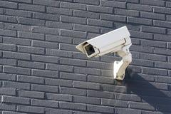 Opinión sobre una cámara de vigilancia blanca que cuelga arriba sobre una pared de ladrillo gris fotografía de archivo