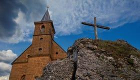 Opinión sobre una iglesia y una cruz delante de un cielo nublado maravilloso fotografía de archivo libre de regalías