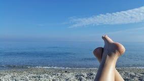 Opinión soleada de los pies de la muchacha cerca del mar Imagen de archivo