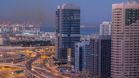 Opinión superior aérea de los rascacielos del puerto deportivo de Dubai antes de la salida del sol de JLT en la noche de Dubai al metrajes