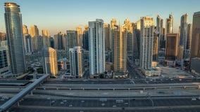 Opinión superior aérea de los rascacielos del puerto deportivo de Dubai durante salida del sol de JLT en la noche de Dubai al tim almacen de video