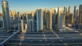 Opinión superior aérea de los rascacielos del puerto deportivo de Dubai durante salida del sol de JLT en la noche de Dubai al tim almacen de metraje de vídeo