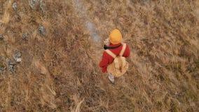 Opinión superior aérea del primer un fotógrafo de la muchacha en un sombrero amarillo con una mochila que va a lo largo de una tr metrajes