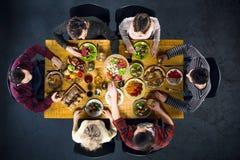 Opinión superior amigos en la tabla con la comida Foto de archivo libre de regalías