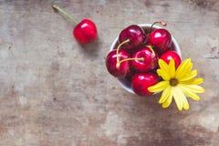 Opinión superior cerezas con una flor amarilla y una paja en una taza blanca en fondo de madera fotos de archivo libres de regalías