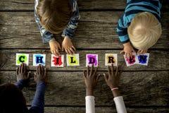 Opinión superior cuatro niños de las razas mixtas que tocan una palabra Childre Fotografía de archivo