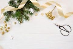 Opinión superior de la decoración de la Navidad de la maqueta y cinta del oro, flatlay en un fondo de madera blanco, con el lugar fotos de archivo