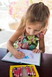 Opinión superior de la niña de las ilustraciones adorables del dibujo sobre los creyones en un cuaderno, un concepto sano y prees fotos de archivo libres de regalías