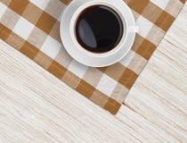 Opinión superior de la taza de café sobre la tabla y el mantel de madera Foto de archivo