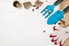 Opinión superior de las herramientas que cultivan un huerto sobre el fondo de madera blanco de los tablones Imagenes de archivo