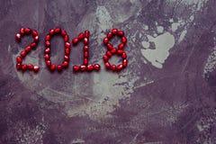 Opinión superior de las semillas de la granada del texto del Año Nuevo 2018 Foto de archivo
