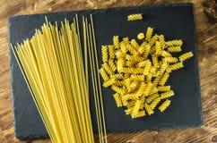 Opinión superior de los espirales de los espaguetis y de las pastas sobre el fondo de la pizarra Foto de archivo