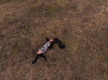 Opinión superior del abejón aéreo una muchacha que miente en un campo que se relaja y que baila Llevar un vestido con las medias fotografía de archivo libre de regalías