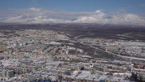 Opinión superior del invierno de la ciudad de Petravlosk Kamchatsky en los volcanes activos del fondo almacen de metraje de vídeo