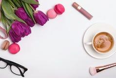 Opinión superior del lugar de trabajo femenino elegante, concepto de la primavera con los tulipanes púrpuras foto de archivo