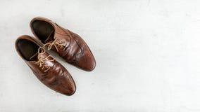 Opinión superior del plumón, zapatos marrones oscuros clásicos gastados de la abarca en el tablero blanco Bandera ancha con el es fotografía de archivo