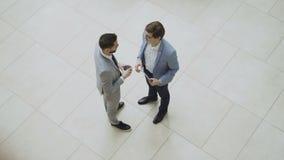 Opinión superior dos hombres de negocios que saludan y que sacuden las manos y que charlan durante descanso para tomar café en el