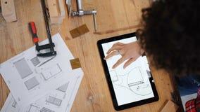 Opinión superior el carpintero de sexo femenino que mira dibujos técnicos en la pantalla de la tableta almacen de metraje de vídeo