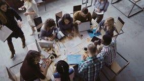 Opinión superior el equipo del negocio de la raza mixta que se sienta en la tabla en la oficina y el trabajo del desván El encarg imágenes de archivo libres de regalías