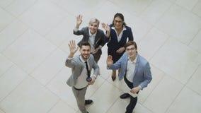 Opinión superior el grupo de hombres de negocios en trajes que discuten gráficos financieros y después que agitan las manos y mir