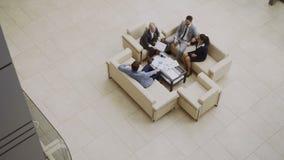 Opinión superior el grupo de hombres de negocios de los colegas que discuten las cartas financieras que se sientan en couchs en p almacen de metraje de vídeo