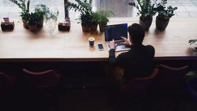 Opinión superior el hombre de la raza mixta que trabaja con el ordenador portátil y el teléfono elegante en el café almacen de metraje de vídeo