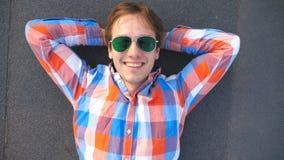Opinión superior el hombre feliz joven en las gafas de sol que mienten en el tejado del edificio alto y de la sonrisa Individuo h metrajes
