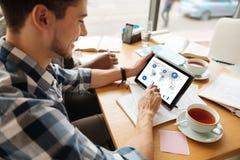 Opinión superior el hombre joven que usa la tableta en el café Imágenes de archivo libres de regalías