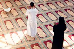 Opinión superior el hombre musulmán y la mujer que ruegan en mezquita Imagenes de archivo