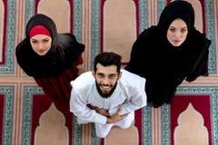 Opinión superior el hombre musulmán y la mujer que ruegan en mezquita Fotografía de archivo