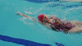 Opinión superior el nadador de sexo femenino aficionado mientras que ella nada estilo de la espalda en el carril de la piscina El almacen de metraje de vídeo