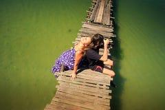 Opinión superior Guy Photos Blond Girl Leans sobre el embarcadero viejo en las zonas tropicales Fotos de archivo