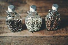 Opinión superior habas verdes y granos de café dentro de la botella clara Fotografía de archivo libre de regalías