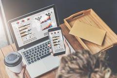 Opinión superior la empresaria que se sienta en la tabla de madera en oficina y que usa smartphone con los gráficos, las cartas y fotografía de archivo