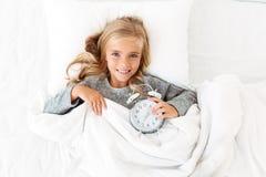 Opinión superior la muchacha rubia alegre que miente en cama con el despertador, Fotos de archivo libres de regalías